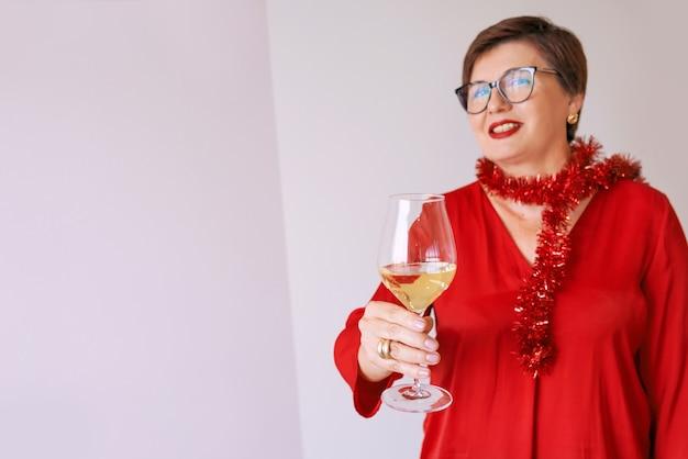 Stijlvolle volwassen senior vrouw in rode blouse met glas witte wijn nieuwjaar vieren