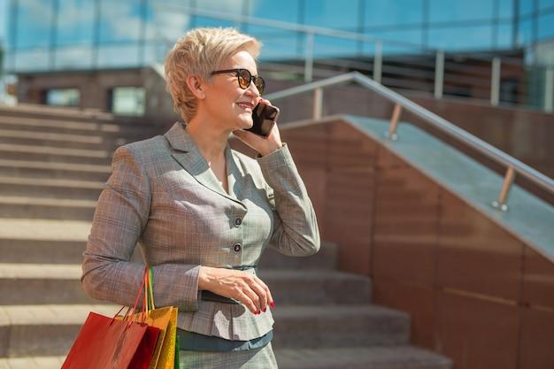 Stijlvolle volwassen vrouw in een pak met een telefoon in haar hand