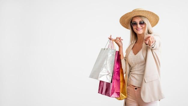 Stijlvolle volwassen vrouw met boodschappentassen met kopie ruimte