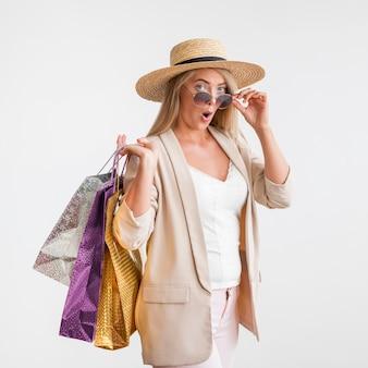 Stijlvolle volwassen vrouw met boodschappentassen