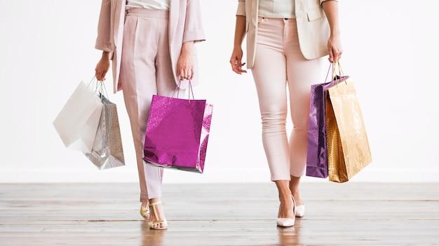 Stijlvolle volwassen vrouwen met boodschappentassen