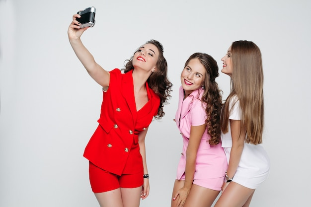 Stijlvolle vriendinnen in sexy pakken glimlachen en nemen zelfportret.