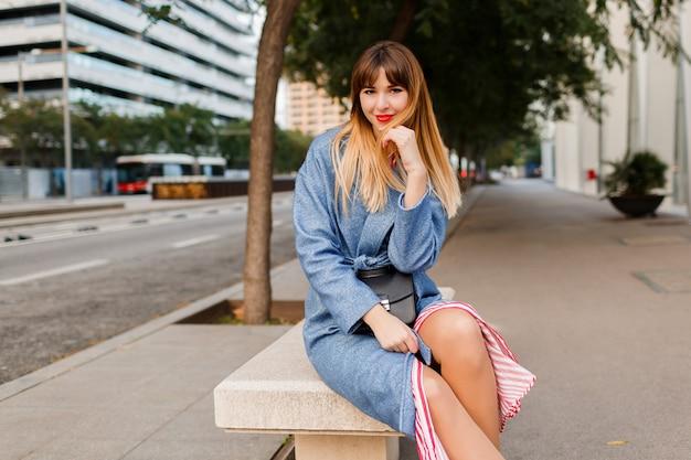 Stijlvolle vrij gelukkige vrouw in blauwe jas zittend op een bankje in de straat