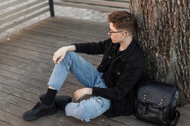 Stijlvolle, vrij stedelijke jongeman in modieuze jeanskleding in modieuze zwarte sneakers met leren rugzak