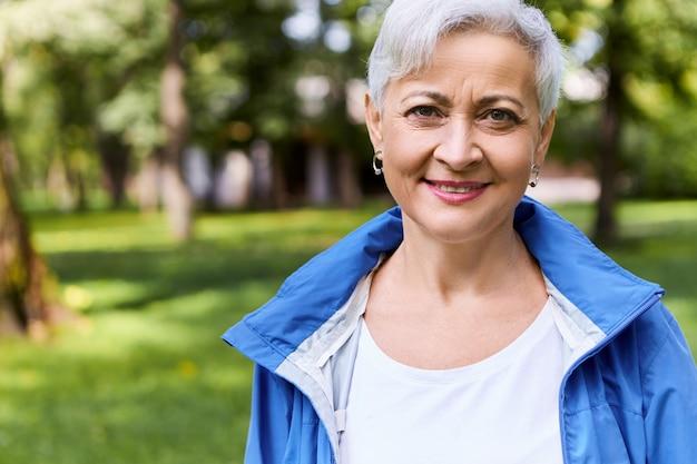Stijlvolle vrolijke vrouw op pensioen met mooie wandeling in zonnig bos op zomerdag met een gelukkige glimlach, genietend van mooi weer en frisse lucht, bomen en groen gras