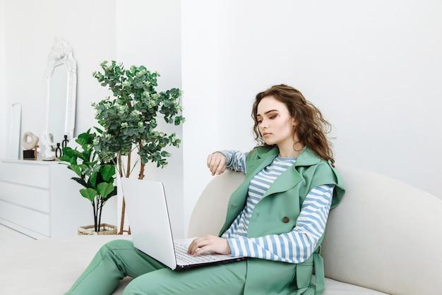 Stijlvolle vrouw aan het werk zittend op de bank met behulp van laptop en internet in de binnenkamer binnenshuis Premium Foto