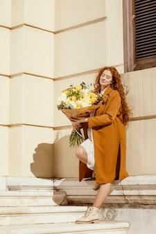 Stijlvolle vrouw buitenshuis met boeket van lentebloemen
