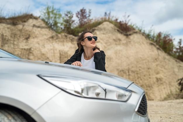 Stijlvolle vrouw die in de buurt van haar auto staat en geniet van vrijheid in de natuur buiten de stad, zomertijd