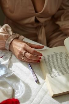 Stijlvolle vrouw die thuis een joint rookt met een boek