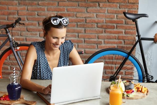 Stijlvolle vrouw draagt een zonnebril op haar hoofd en maakt een videogesprek met haar vriend via gratis wifi op een generieke laptop