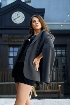 Stijlvolle vrouw, gekleed in korset en jas poseren buitenshuis.