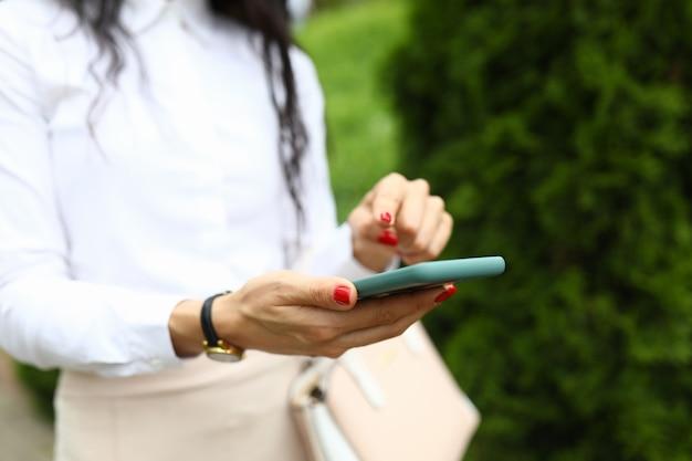 Stijlvolle vrouw houdt een smartphone in haar handen en wijst met haar vinger naar het scherm