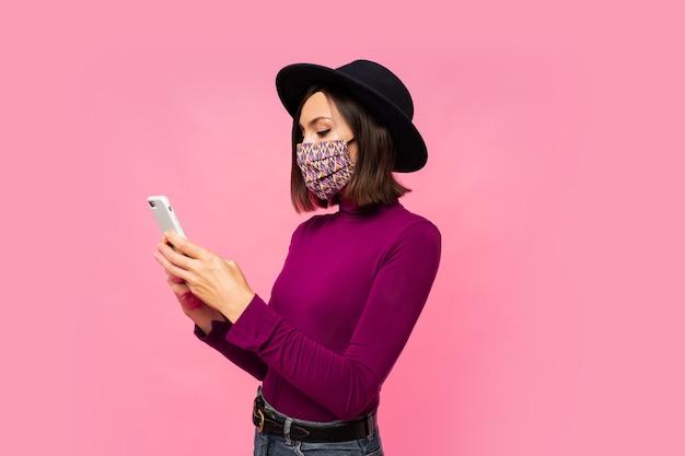 Stijlvolle vrouw in beschermend masker en zwarte hoed met behulp van mobiele telefoon, permanent.