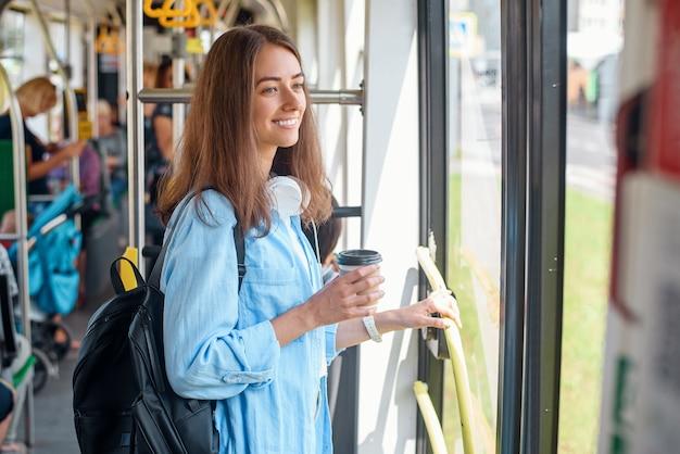 Stijlvolle vrouw in blauw shirt genieten van reis in de moderne tram of bus, staat met een kopje koffie in het openbaar vervoer.