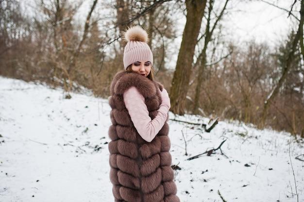 Stijlvolle vrouw in bontjas en hoofddeksels in winter forest.