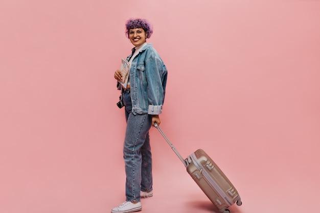 Stijlvolle vrouw in brede spijkerjas houdt koffer en vliegtickets. l.