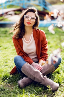Stijlvolle vrouw in casual lente outfit zittend op gras in zonnig warm park