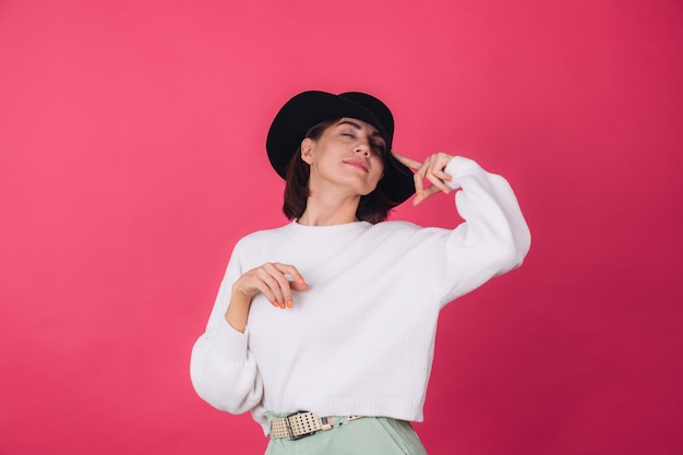 Stijlvolle vrouw in casual witte trui en hoed op roze rode muur