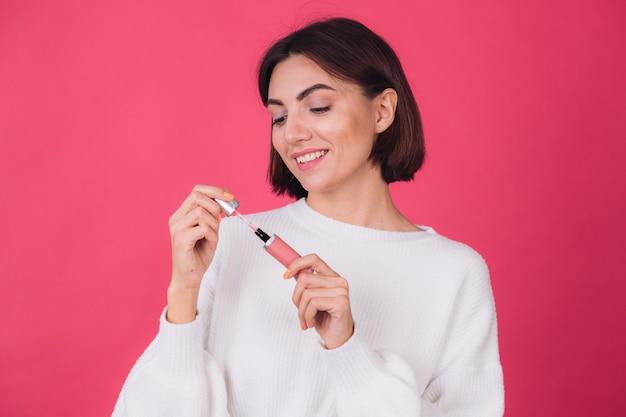 Stijlvolle vrouw in casual witte trui op roze rode muur