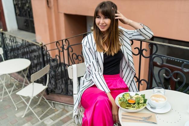 Stijlvolle vrouw in casual zomeroutfit die geniet van het ontbijt tijdens de koffiepauze.