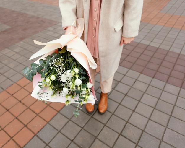 Stijlvolle vrouw in de stad met boeket bloemen