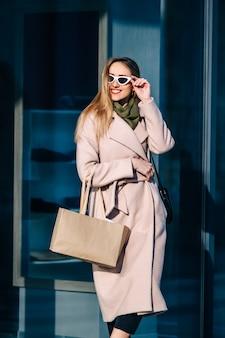Stijlvolle vrouw in een jas en zonnebril in de buurt van de winkel