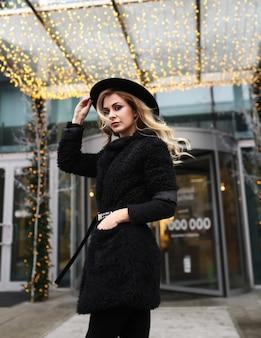 Stijlvolle vrouw in een warme zwarte jas en hoed op straat tegen een achtergrond van kerstlicht