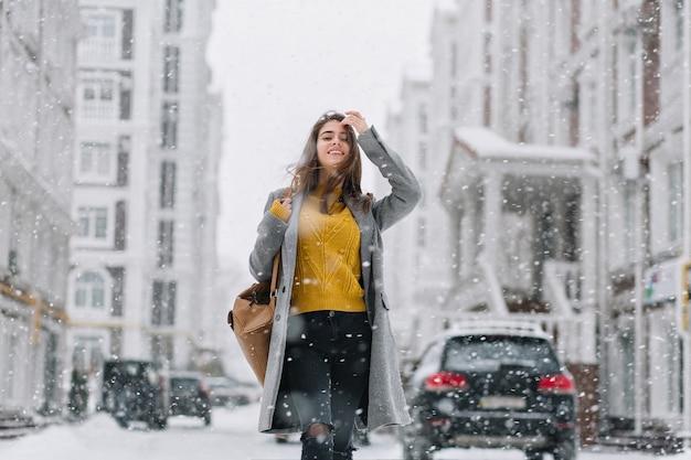 Stijlvolle vrouw in gebreide gele trui poseren onder sneeuwval op straat. outdoor portret van schattige dame in grijze jas genieten van sneeuw