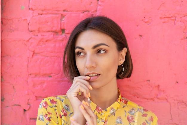 Stijlvolle vrouw in gele zomerjurk op roze bakstenen muur gelukkig kalm en positief Premium Foto