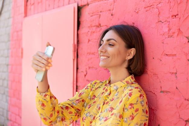 Stijlvolle vrouw in gele zomerjurk op roze bakstenen muur gelukkig positief selfie op mobiele telefoon te nemen