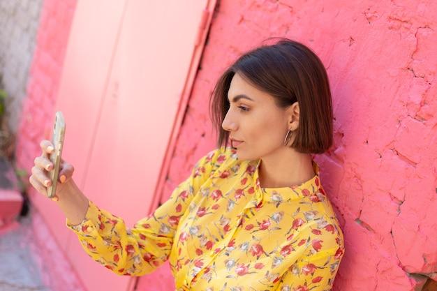 Stijlvolle vrouw in gele zomerjurk op roze bakstenen muur gelukkig positief selfie op mobiele telefoon te nemen Premium Foto