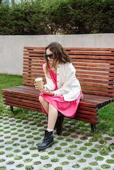 Stijlvolle vrouw in glazen model poseren zittend op een bankje met een koffiekopje