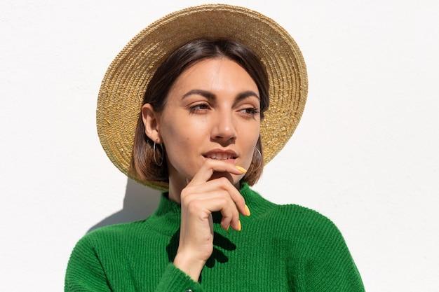 Stijlvolle vrouw in groene casual trui en hoed buiten op witte muur kalme en zelfverzekerde glimlach
