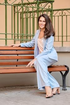 Stijlvolle vrouw in hemelsblauw broekpak met rust op een bankje in de buurt van het kantoor