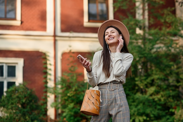 Stijlvolle vrouw in hoed achter prachtige gebouwen op de achtergrond en luistert naar muziek met koptelefoon.
