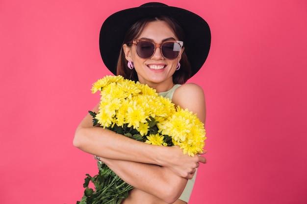 Stijlvolle vrouw in hoed en zonnebril, groot boeket gele asters knuffelen, lentestemming, kalme glimlachende geïsoleerde ruimte