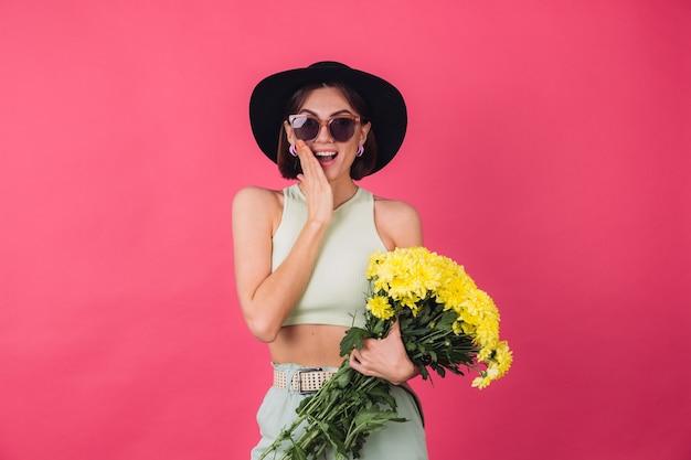 Stijlvolle vrouw in hoed en zonnebril, met groot boeket gele asters, lentestemming, opgewonden verbaasde emoties open mond geïsoleerde ruimte