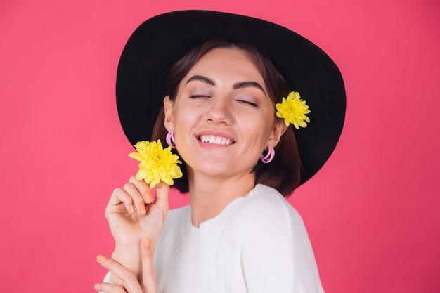 Stijlvolle vrouw in hoed, lachend met twee gele asters, lentestemming, gelukkige emoties geïsoleerde ruimte bijten lip