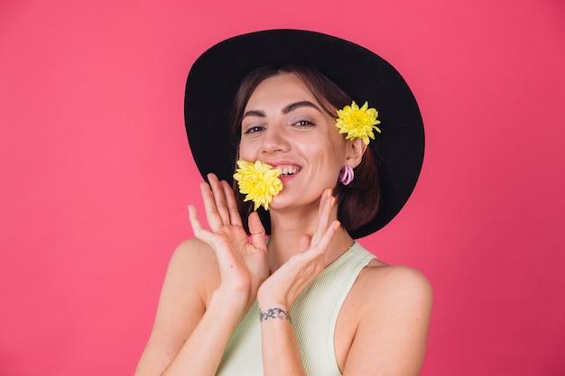 Stijlvolle vrouw in hoed, lachend met twee gele asters, schattig houden een bloem in mond lentestemming, gelukkige emoties geïsoleerde ruimte