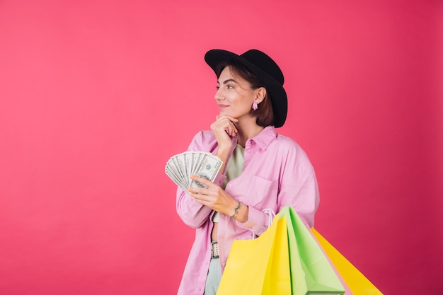 Stijlvolle vrouw in hoed op roze rode muur
