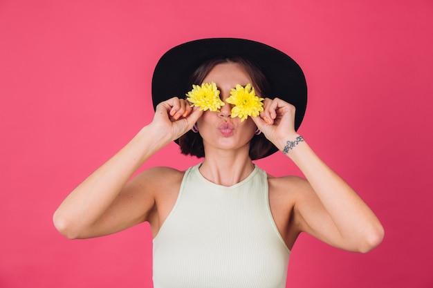 Stijlvolle vrouw in hoed, stuur luchtkusbedekkingsogen met gele asters, lentestemming, gelukkige emoties geïsoleerde ruimte