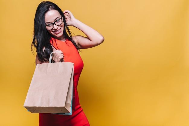 Stijlvolle vrouw in jurk met boodschappentassen