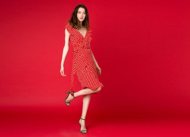 Stijlvolle vrouw in jurk op rode manier