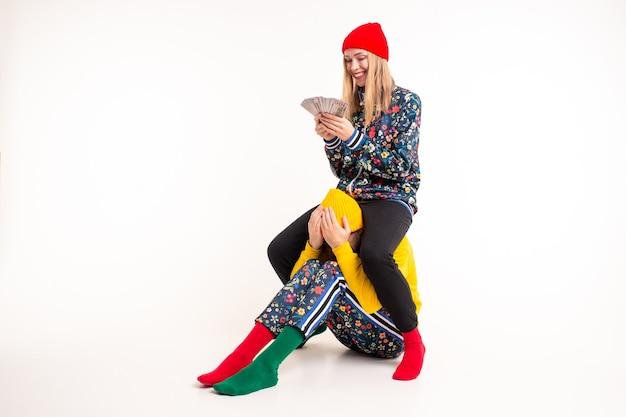 Stijlvolle vrouw in kleurrijke kleding die geld in plaats van liefde kiest