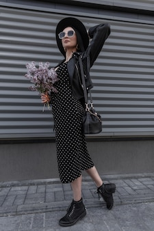 Stijlvolle vrouw in modieuze zwarte kleding in vintage hoed in trendy zonnebril met tas met boeket verse lila bloemen staat in de buurt van grijze metalen muur in straat. mooi fijn meisje in lente zwarte outfit.