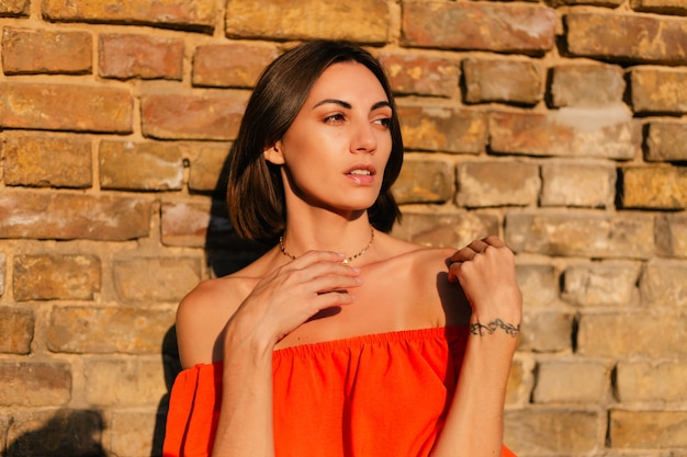 Stijlvolle vrouw in oranje kleding bij zonsondergang bij bakstenen muur