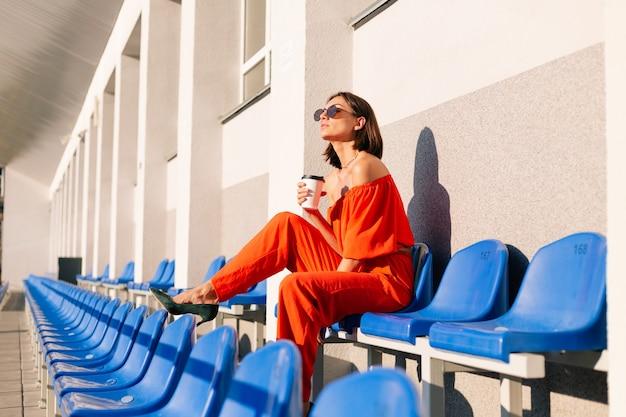 Stijlvolle vrouw in oranje kleding bij zonsondergang bij fietspad stadion met kopje koffie en mobiele telefoon