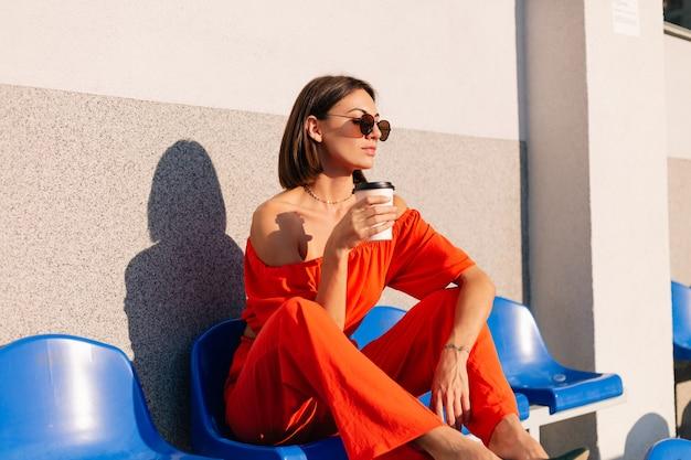 Stijlvolle vrouw in oranje kleding bij zonsondergang bij fietspad stadion met kopje koffie