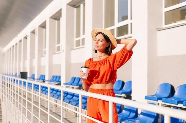 Stijlvolle vrouw in oranje kleding bij zonsondergang bij fietspad stadion poseren met kopje koffie