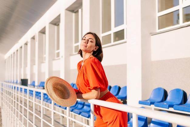 Stijlvolle vrouw in oranje kleding bij zonsondergang bij fietspad stadion poseren